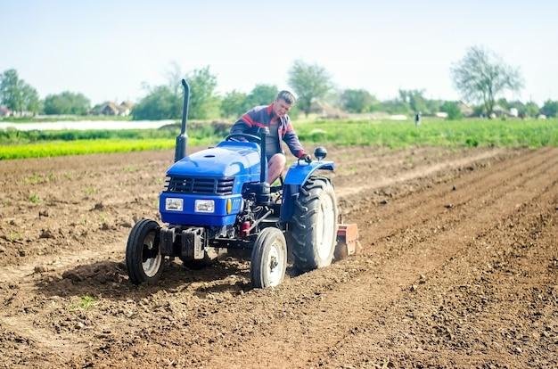 Um fazendeiro em um trator cultiva um campo de cultivo moagem de solo, se desintegrando e se misturando