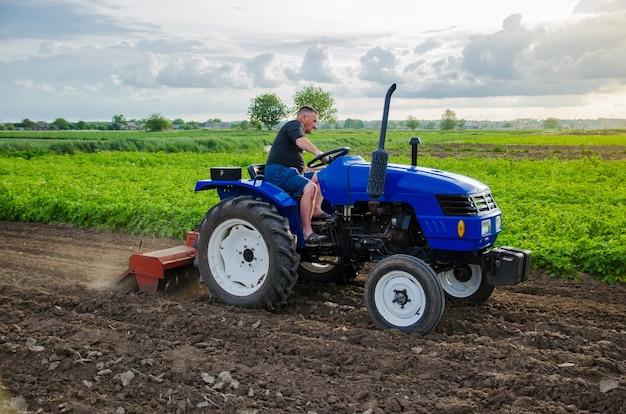 Um fazendeiro está cultivando um campo de fazenda triturando o solo, triturando antes de cortar as fileiras