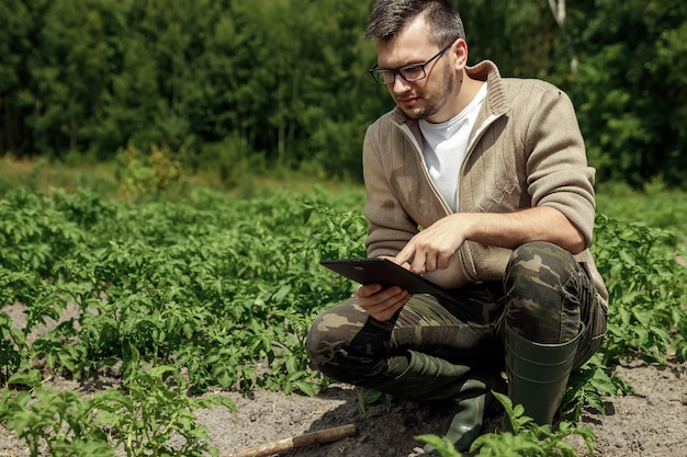 Um fazendeiro masculino que senta-se no campo e que usa uma tabuleta. moderna aplicação de tecnologias em atividades agrícolas.