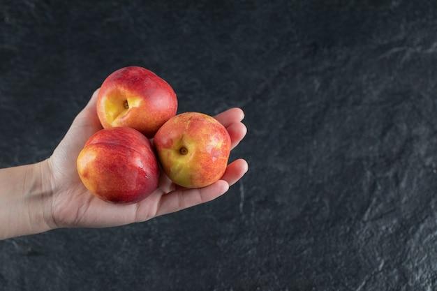 Um fazendeiro segurando pêssegos vermelhos na palma da mão