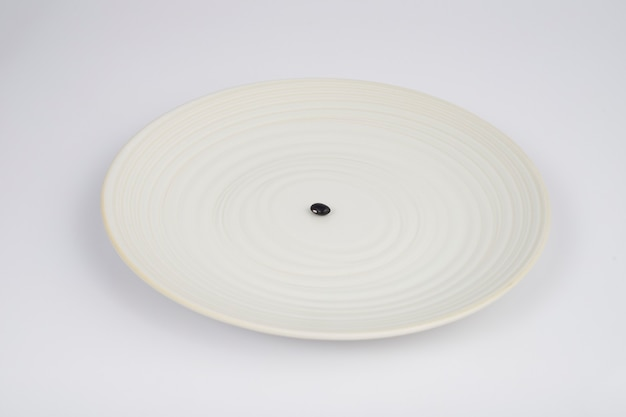 Um feijão preto em um prato fundo branco.