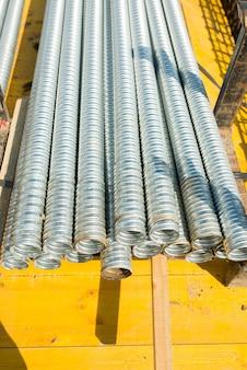 Um feixe de tubos de metal corrugado em um canteiro de obras