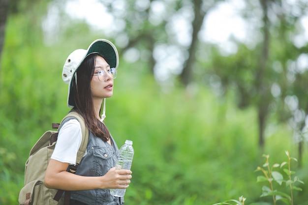 Um feliz caminhante caminha pela selva com uma mochila.