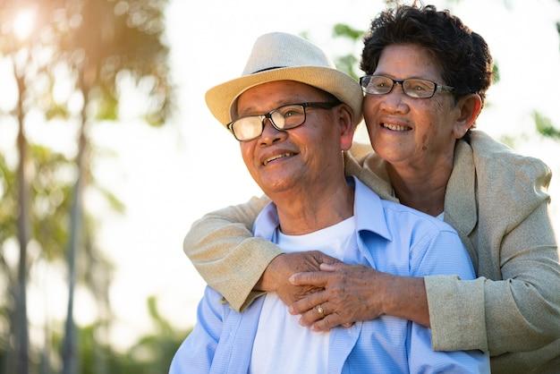 Um feliz casal sênior asiático velho e mulher sorrindo e rindo no jardim