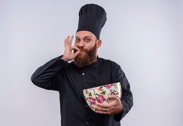 Um feliz chef barbudo de uniforme preto segurando uma xícara enorme e mostrando um gesto de ok enquanto olha para a câmera em uma parede branca
