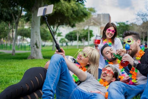 Um feliz grupo de amigos, vestidos com máscaras e acessórios de aniversário, tirando fotos com o bastão de selfie na grama do parque.