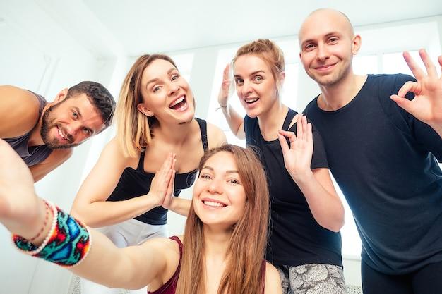 Um feliz grupo de pessoas de homem e mulher praticando ioga no estúdio e fazendo selfies ao telefone. grupos de meditação e apoio na aula de ioga. homens e mulheres se divertem.