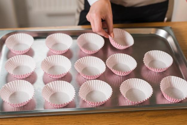 Um, femininas, mão, organizando, a, cupcake, invólucros, ligado, aço inoxidável, bandeja