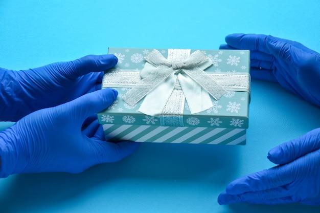 Um feriado durante uma pandemia um homem com luvas médicas passa um presente parabéns aos médicos