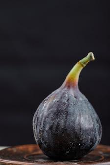 Um figo no pratinho e na mesa de mármore, close-up.