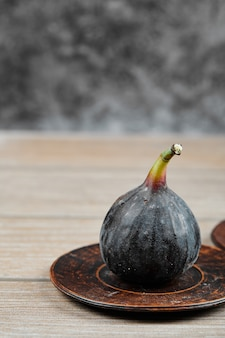 Um figo no prato pequeno e na mesa de madeira.