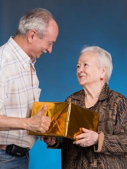 Um filho adulto e uma mãe idosa com uma caixa de presente