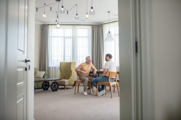 Um filho e um pai conversando e tomando chá juntos