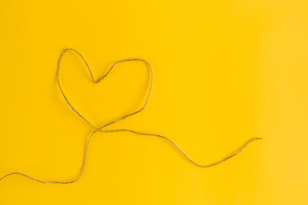 Um fio em forma de coração em fundo amarelo. estilo liso