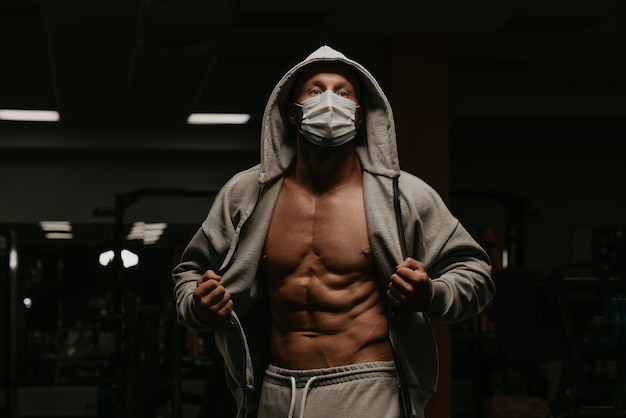Um fisiculturista com capuz e máscara facial para evitar a propagação do coronavírus está abrindo um moletom para demonstrar seu físico atlético. um cara esportivo com uma máscara cirúrgica está posando após um treino em uma academia.