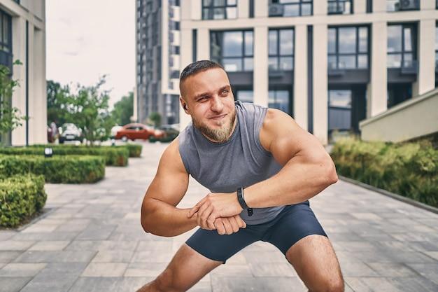 Um fisiculturista de cabelo curto com barba e um fone de ouvido no ouvido se espreguiça se espreguiçando na rua perto de edifícios de escritórios