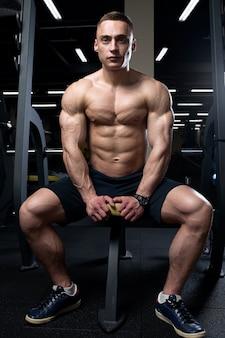 Um fisiculturista desfiado sem camisa com pele pálida está sentado em um banco e apertando seus músculos peitorais em uma academia.