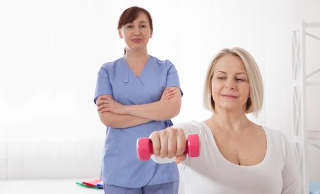 Um fisioterapeuta ajuda uma mulher mais velha a se recuperar de uma lesão através de exercícios com halteres