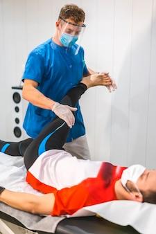 Um fisioterapeuta com máscara e tela plástica trabalhando com um paciente. fisioterapia com medidas de proteção para a pandemia de coronavírus, covid-19. osteopatia, quiromassagem terapêutica