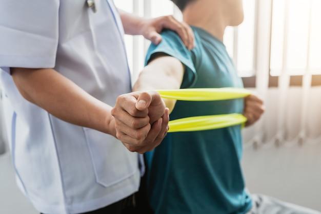 Um fisioterapeuta está ajudando um paciente a esticar o braço com um pano na clínica.