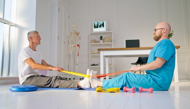 Um fisioterapeuta treina com segurança um paciente usando equipamento médico de exercícios na reabilitação ...