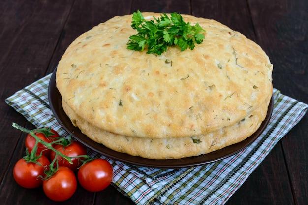 Um flapjack grosso - pão árabe com verdes sobre um fundo escuro de madeira. um prato tradicional asiático.