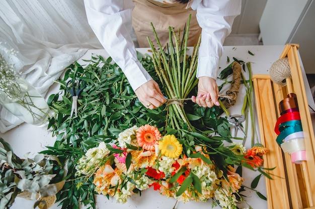 Um florista amarra um buquê de flores frescas com barbante em sua mesa cheia de folhas cortadas