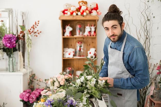 Um florista masculino criando o buquê de flores em sua loja