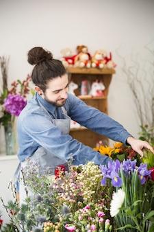 Um florista masculino organizando a flor colorida fresca na loja