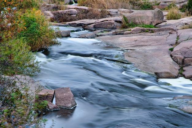 Um fluxo fantástico e rápido corre entre pedras brancas úmidas cobertas com grama dourada amarelada em um outono frio na natureza pitoresca da ucrânia