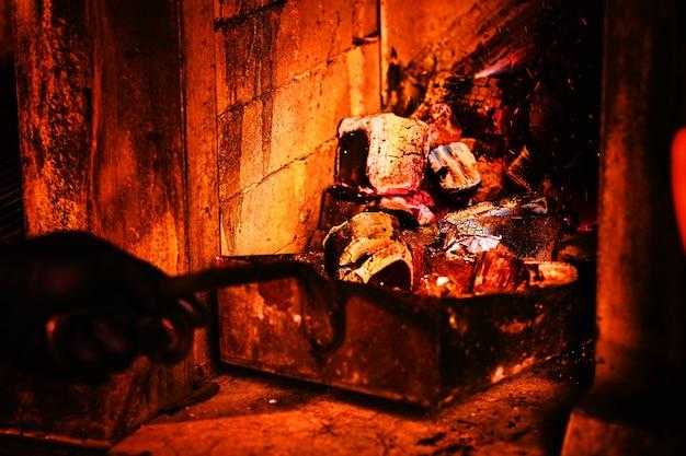 Um fogão em um restaurante com brasas. scoop joga carvão na fornalha com carvão picado.