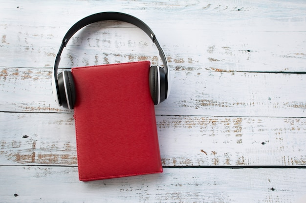 Um fone de ouvido usando no livro vermelho, conceito de tempo relaxante