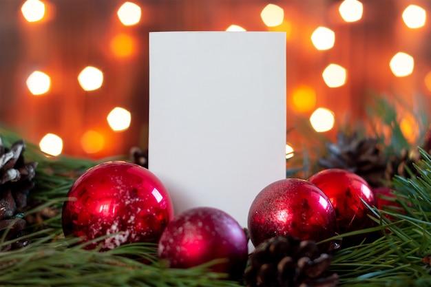 Um formulário branco em branco para o texto de saudação em um galho de uma árvore de natal com bolas e cones vermelhos de brinquedo