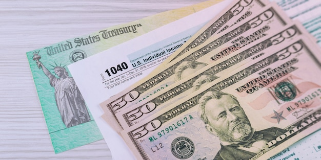 Um formulário de imposto de renda de imposto federal dos eua 1040 com dinheiro e cheque de reembolso