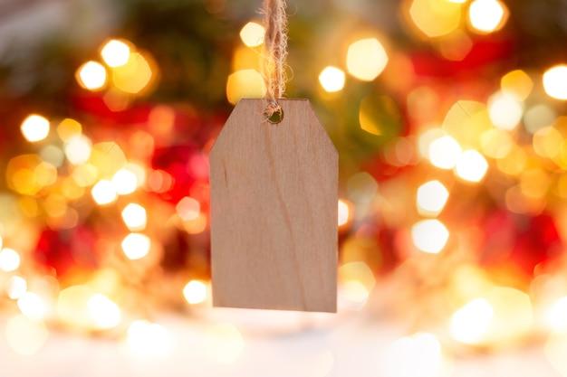 Um formulário em branco de madeira para saudar o texto de natal está pendurado em um fundo desfocado de luzes de bokeh