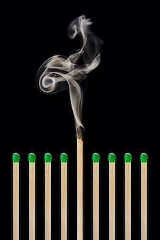 Um fósforo apagado em um grupo de fósforos verdes, desgaste emocional, estresse, trabalho, vida, equilíbrio