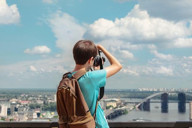 Um fotógrafo do homem fotografa uma vista da cidade bonita, vista da parte traseira.