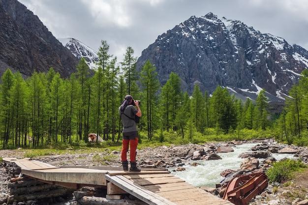 Um fotógrafo em uma velha ponte de madeira tira fotos de montanhas distantes. vista deslumbrante sobre o vale da montanha, sob o céu azul. aktru. montanhas altai.