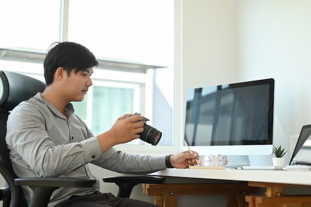 Um fotógrafo está verificando as visualizações na câmera e sentado em sua área de trabalho