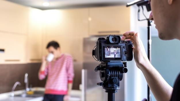 Um fotógrafo fotografando um homem bebendo na cozinha