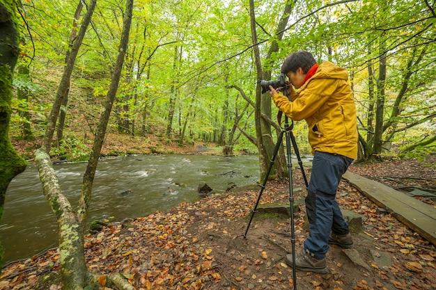 Um fotógrafo tira fotos de uma bela vista do rio e da floresta