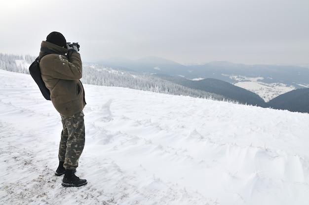 Um fotógrafo tirando uma foto de uma incrível montanha de inverno do topo de uma montanha.