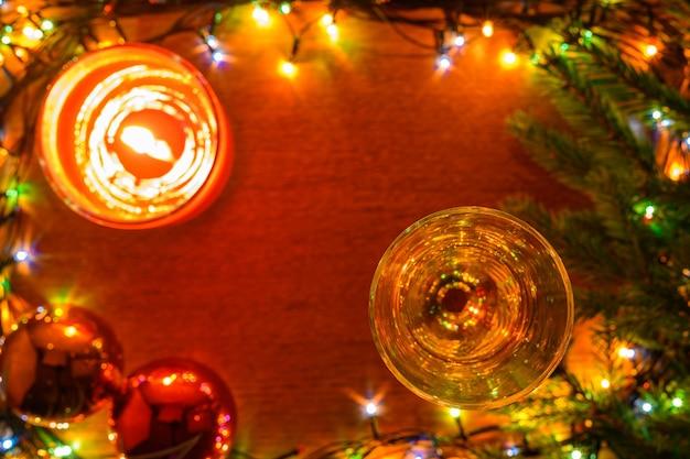Um fougere de vinho espumante, uma vela, duas bolas brilhantes em um fundo desfocado de madeira.