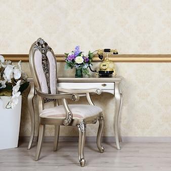 Um fragmento de um interior retrô com uma cadeira e uma mesa na qual está localizado um telefone e um vaso de flores