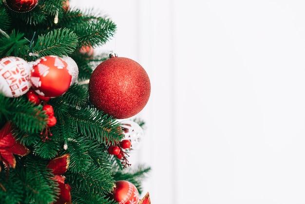 Um fragmento de uma árvore de natal decorada com bolas vermelhas em um fundo de parede branca, conceito de natal e ano novo