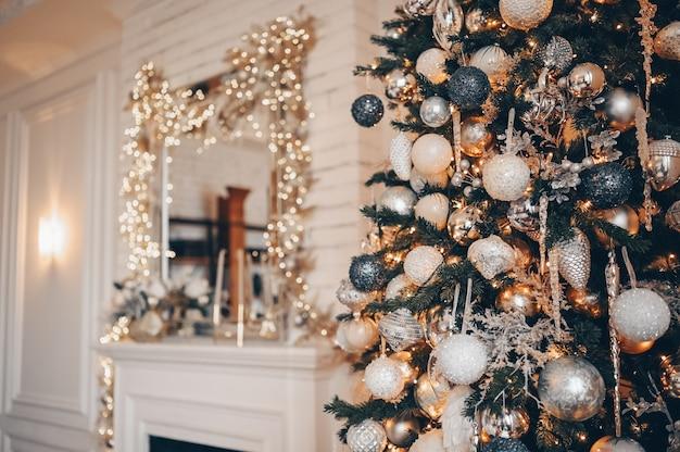 Um fragmento de uma árvore de natal decorada em cores quentes douradas no interior de um quarto clássico branco