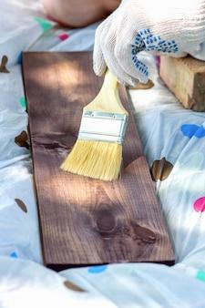 Um fragmento de uma mão enluvada que pinta uma tábua de madeira com um pincel largo. fotografia vertical