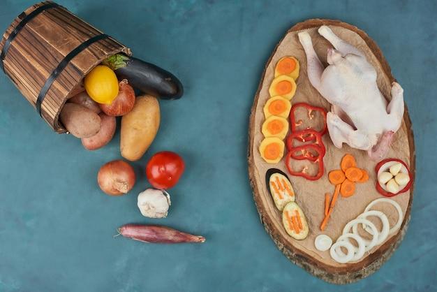 Um frango com legumes em uma placa de madeira.