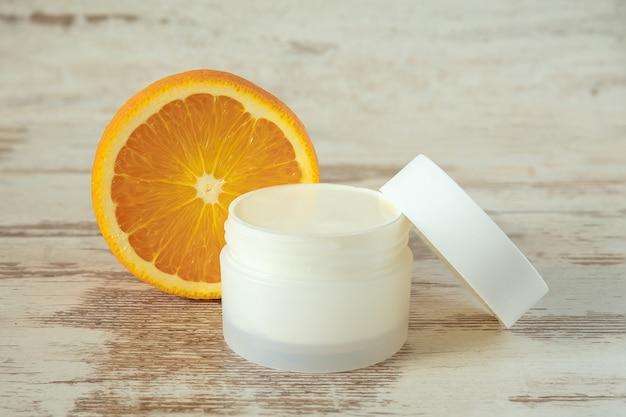 Um frasco branco com creme cosmético e uma laranja em um fundo de madeira