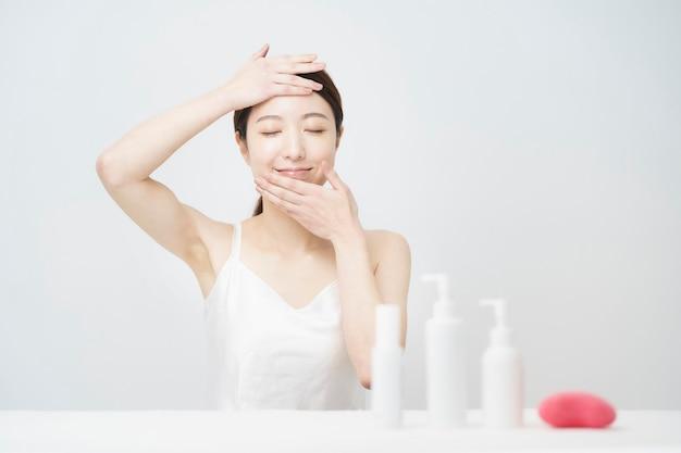 Um frasco branco com uma mulher que toca o rosto para cuidar da pele